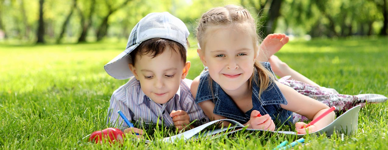 barn i park läser bok